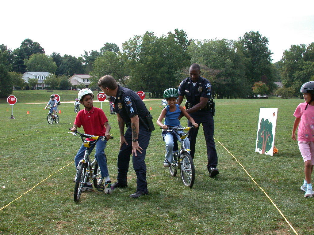 Two cops helping kids ride bikes