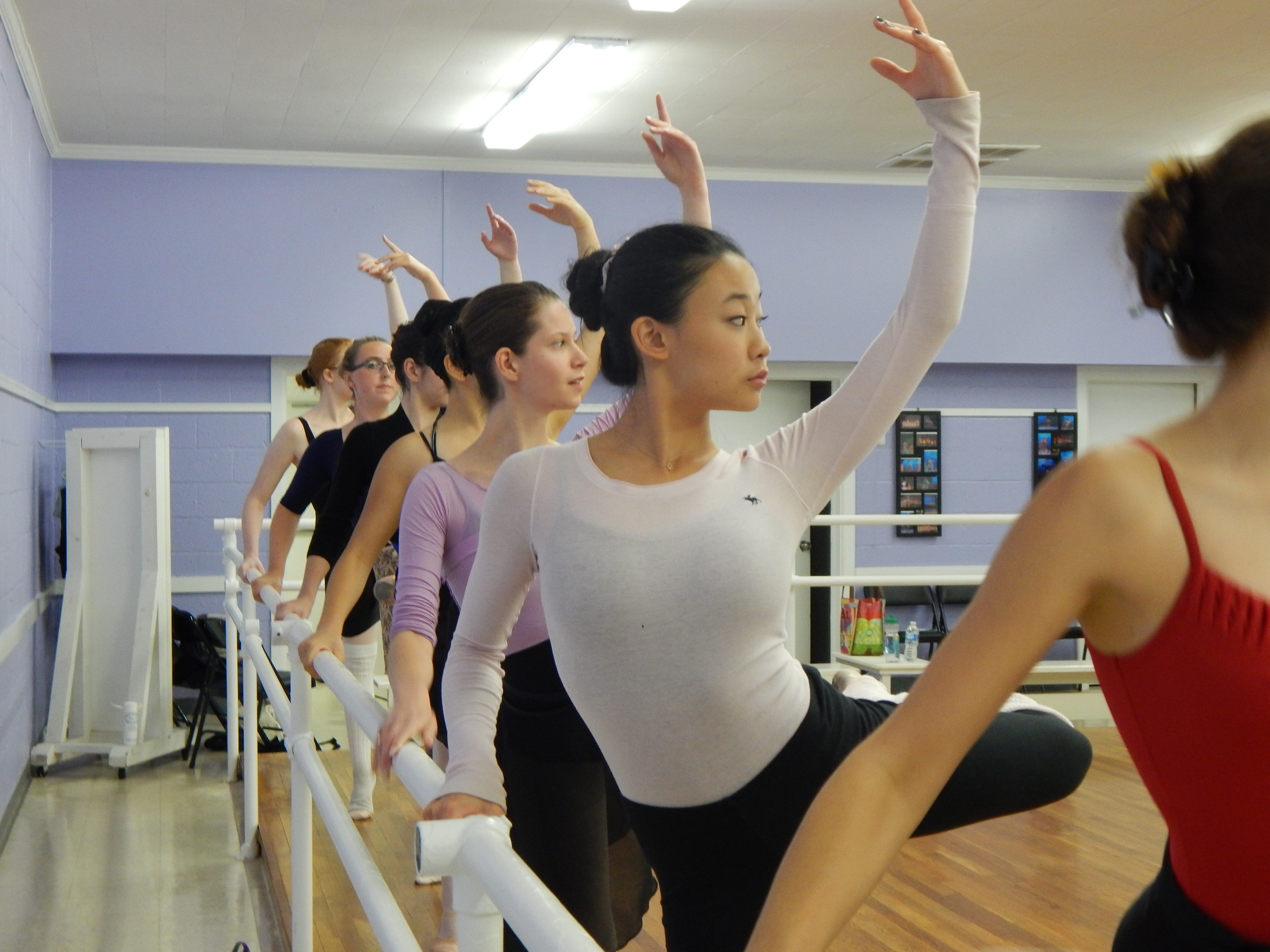 Row of ballet dancers posing on a barre