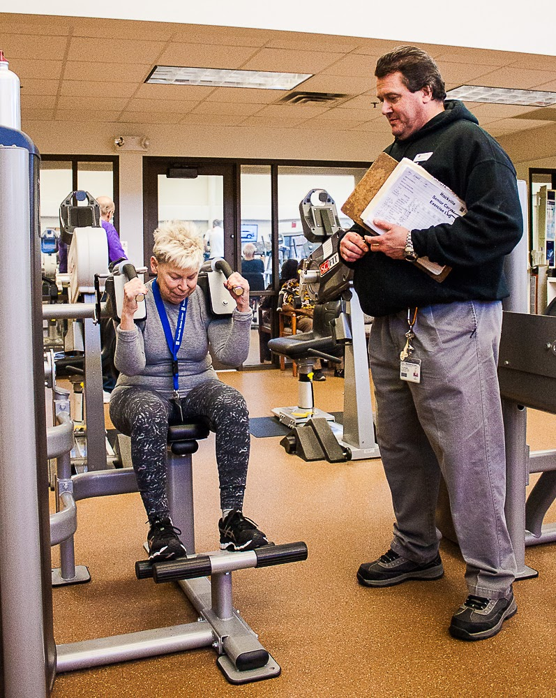 Person on a fitness machine being coached by a trainer