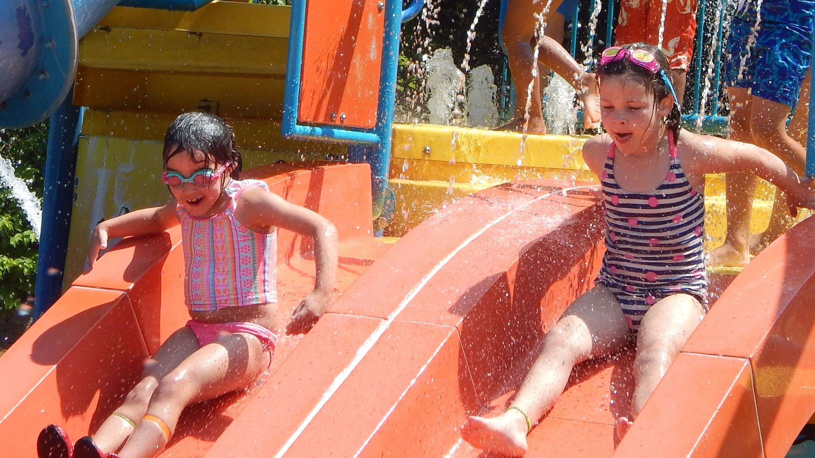 Two kids sliding down a water slide