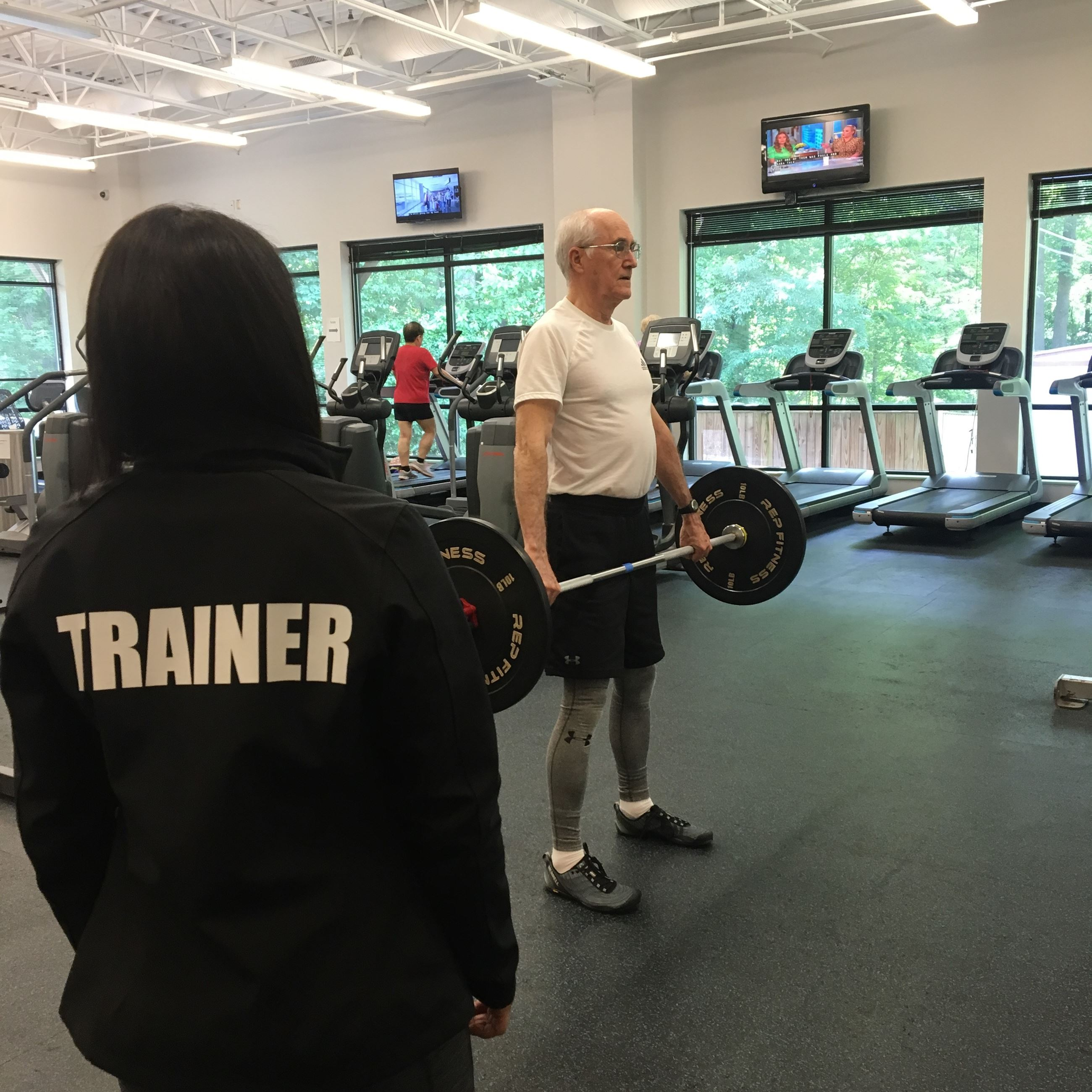 man weightlifting with personal trainer